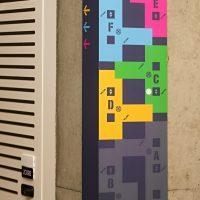 Barevný plánek budovy na rohu betonové stěny, označení místností písmeny, šipky