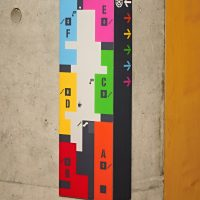 Barevný plánek budovy na rohu betonové zdi, označení místností písmeny, šipky
