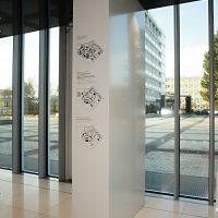 Tři černobílé orientační plánky s vysvětlujícím textem na bílém dibondu, skleněné dveře, výhled na venkovní prostranství ČZU