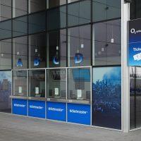 Pokladny s označením A, B, C, D, a loga ticketmaster, prodej vstupenek do O2 Universum, světelná výstrč na rohu prosklené budovy