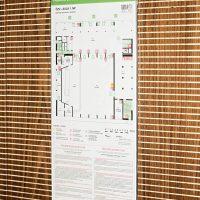 Požární evakuační plán na bílé dibondové desce na dřevěném obložení se strukturou dřeva a frézovanými linkami