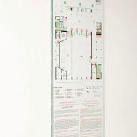 Požární evakuační plán, skleněná deska na bílé zdi