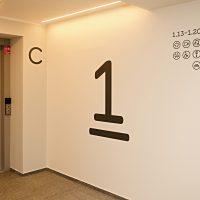 Černá podtržená číslice 1 na stěně, označení patra, plotrované navigační piktogramy, dveře výtahu s čísly pater, písmeno C na stěně
