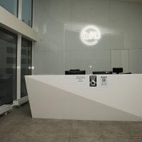 Pult moderní recepce, za ní na stěně světelné 3D logo bit