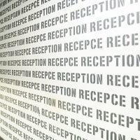 Šedé opakované nápisy RECEPCE a RECEPTION na bílé stěně v ústředí ČSOB