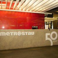 Betonový recepční pult, bílé 3D logo Metrostav, nápis 50 METROSTAV 1971–2021, červená stěna