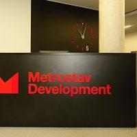 Černý recepční pult, červené 3D logo Metrostav Development, červeno-bílé hodiny na černé stěně