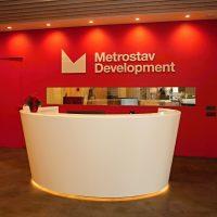 Značení recepce, bílé logo Metrostav Development z plexiskla na červené zdi, bílý oválný stůl