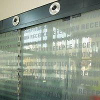 Opakovaný nápis RECEPCE a RECEPTION, skleněná stěna, žaluzie, bodové osvětlení