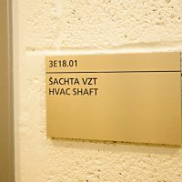 Hliníková dveřní cedulka s černým gravírovaným označením 3E18.01 a textem ŠACHTA VZT a HVAC SHAFT, bílá strukturovaná zeď