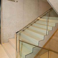 Nápis 1 NP BALKON s šipkou na stěně, označení směru, schodiště se skleněným zábradlím a nerezovými madly