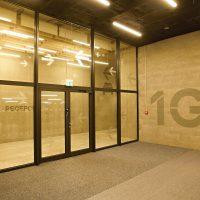 Prosklená stěna v komplexu garáže s únikovými šipkami a nápisem recepce, malované označení 1G na cihlové stěně
