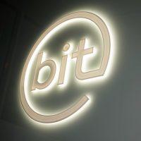 Bílé světelné 3D logo bit na tmavě šedé stěně