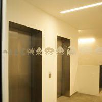 Výtahy za skleněnou stěnou s motivy ze starých počítačových her