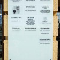 Skleněná informační tabule na zdi budovy, černé nápisy a znaky na mléčném skle, označení ordinací v budově