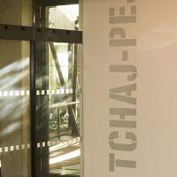 Svislý malovaný nápis TCHAJ-PEJ na stěně chodby administrační budovy, skleněné dveře