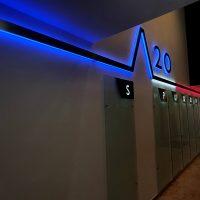 Podsvícená modro-bílo-červená lišta na chodbě kancelářské budovy, světelný nápis 20, skleněné informační tabule s označením pater