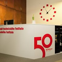 Bílý recepční pult, červené označení úseků, logo 50 Metrostav, červeno-černé hodiny lepené na bílé zdi