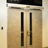 Černá navigační tabule se stříbrným gravírovaným textem nad šedými dvoukřídlými dveřmi s úzkými skleněnými okénky
