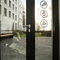 Černé symboly květiny, grilu a kamery v kroužku, skleněné vchodové dveře s černými rámy, řezaná grafika, výhled ven z budovy