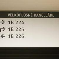 Stropní navigační tabule s kovovými závěsy, nápis Velkoplošné kanceláře, šipky s označením místností