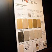 Bílá deska se vzorky podlah, obkladů, dveří a klik, nápis Byty u parku Na Vackově, černá stěna