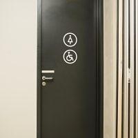 Bílé značení WC na černých dveřích, piktogram dámy a invalidé v kroužku, řezaná grafika