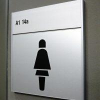 Označení WC ženy, černý symbol ženy, značení A1 14a, stříbrná tabulka slim slatz