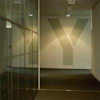 Velké písmeno Y na bílé stěně chodby v administrační budově, skleněná příčka