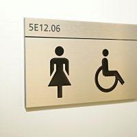 Hliníková dveřní tabulka s černým gravírovaným označením 5E12.06 a piktogramy WC ženy a invalidé, bílá strukturovaná zeď