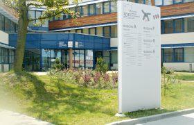 Bílý totem s orientačními nápisy stojící na trávníku před komplexem kancelářských budov za slunného dne