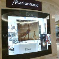 Značení výlohy luxusní prodejny v obchodným centru, laminovaná černá folie s logem Dior lemuje sklo, svítící bílé logo Marionnaud na černé desce nad výlohou, v pozadí další obchody