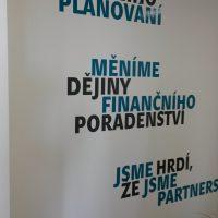 Modré a černé slogany Partners z plotrové folie nalepené na bílé zdi, zelené rostliny na podlaze