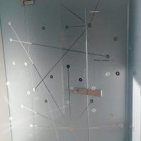 Skleněná příčka s dveřmi polepená pískovanou folií s vyřezanými motivy kruhů a přímek