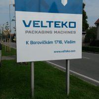 Reklamní cedule firmy VELTEKO s šipkou přesahující okraj, stojící na dvou sloupech v exteriéru na trávníku, v pozadí část silnice, stromy, obloha
