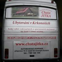 Zezadu vyfocený stříbrný autobus, na okně polep - vlevo fotka chaty a vpravo nápis červený Chata JITKA, pod oknem červené nápisy a piktogramy, dole červeně web a pod ním černý nápis AUTOBUSOVÁ DOPRAVA, telefon, dole spz, ve tmě