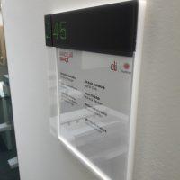 Informační tabule z černého a bílého plexiskla, text jako označení kanceláří, nalepeno na bílé strukturované zdi
