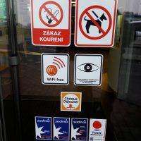 Bezpečnostní informační tabulky s piktogramy nalepené na skleněných dveřích