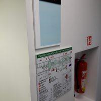 Bílo-modrá tabule s červeným nápisem SAFETY na černém obdélníku, pod ní požární evakuační plán na informační tabuli, nalepeno na bílé zdi, ve výklenku hasicí přístroj