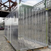 Kontejnerová stavební buňka na pražské náplavce polepená zrcadlovou folií, pohled z pravého předního rohu, detail Železničního mostu, zábradlí