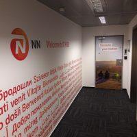 Fototapeta s logem NN a oranžovými nápisy ve světových jazycích nalepená na bílé stěně chodby, polep dveří barevnou fototapetou se sloganem a fotografií, černá podlaha