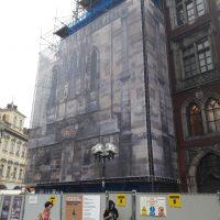 Staroměstský orloj z boku, obehnán lešením, zakrytý potištěným bannerem, který ho imituje