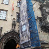 Horolezci instalující potištěný banner na lešení na Staroměstském orloji