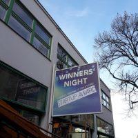 Velká reklamní výstrč na fasádě dvou podlažní budovy, nápis WINNERS' NIGHT, řady oken a výloh, pojízdná montážní plošina
