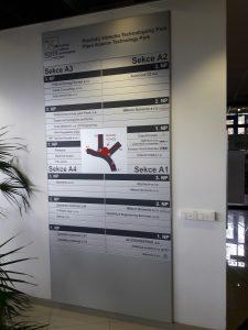 Stříbrná informační tabule s černými nápisy označení pater a firem, uprostřed orientační plán budov komplexu Plzeňský vědecko Technologický Park