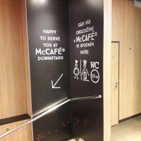 Laminovaná fototapeta s informačním značením uvnitř McCafé, nalepená na rohové stěně nad schody