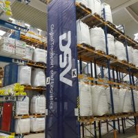 Prostředí skladu, na velkém regálu spoustu bílých pytlů ve třech stupních, regál zleva pokryt modrým bannerem s bílými nápisy, v pozadí další regály