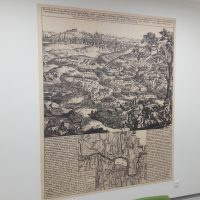 Potištěná fototapeta s motivem staré mapy a doprovodným textem, nalepená na bílé zdi