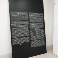 Černá tabule opřená o bílou stěnu, polep černou matnou plotrovou fólií, bloky textu z bílé zrcadlové folie