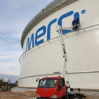 Dva pracovníci na vysokozdvižné plošině provádí malbu modrého loga Mero na naftovou nádrž